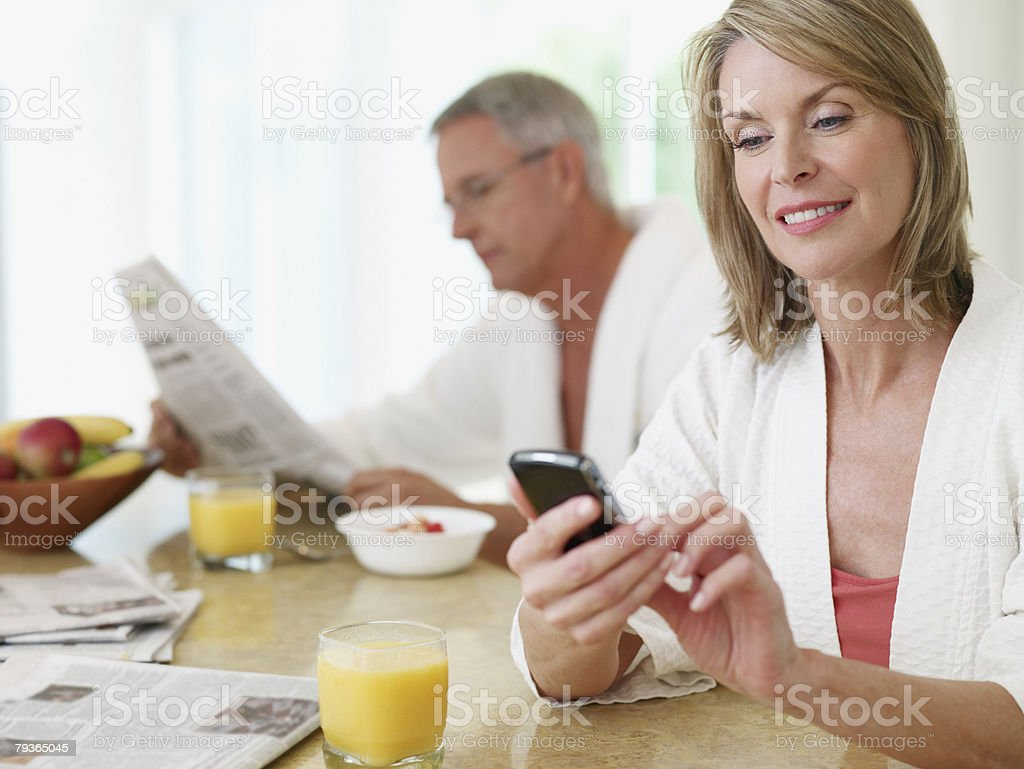 Couple in kitchen eating breakfast and reading newspaper stock photo