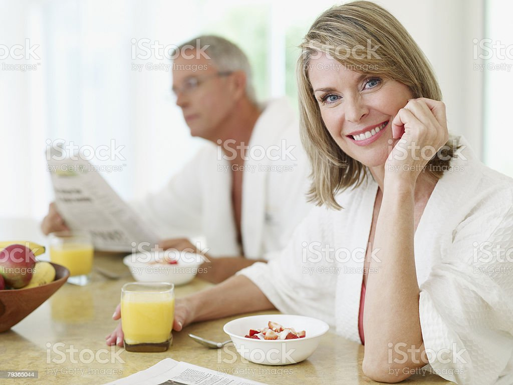 Couple in kitchen having breakfast and reading newspaper stock photo