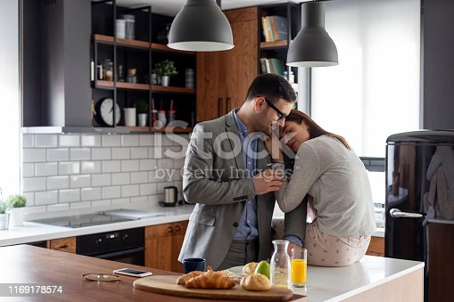 istock Couple in kitchen, he is ready to go to office while she sitting in piyama 1169178574