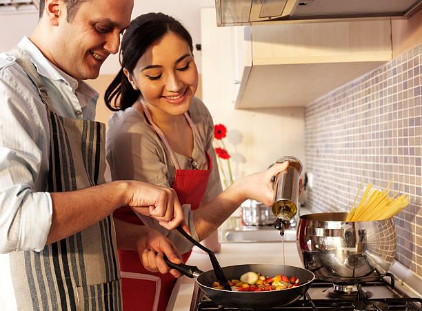 couple in kitchen - oil kitchen stockfoto's en -beelden