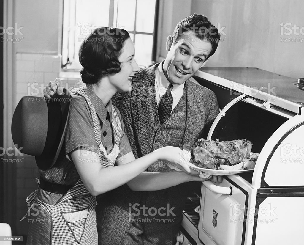 Couple in kitchen, wife taking roast from oven, (B&W) stock photo