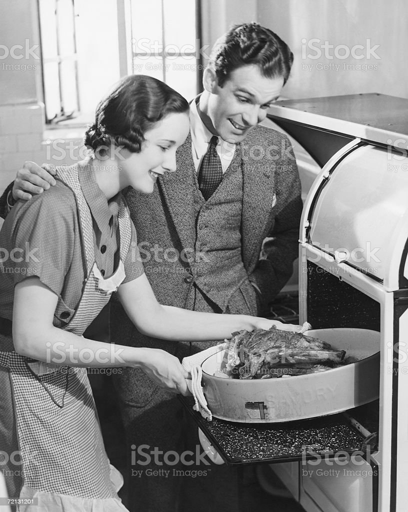 Couple in kitchen, wife taking roast from oven (B&W) stock photo