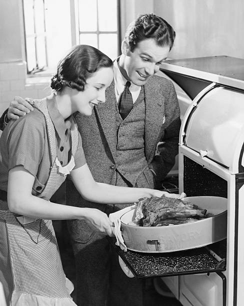 Couple in kitchen, wife taking roast from oven (B&W)  cooking black and white stock pictures, royalty-free photos & images
