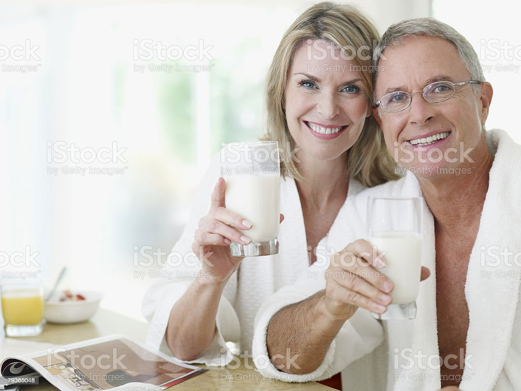 Couple in kitchen with glasses of milk and magazine stock photo