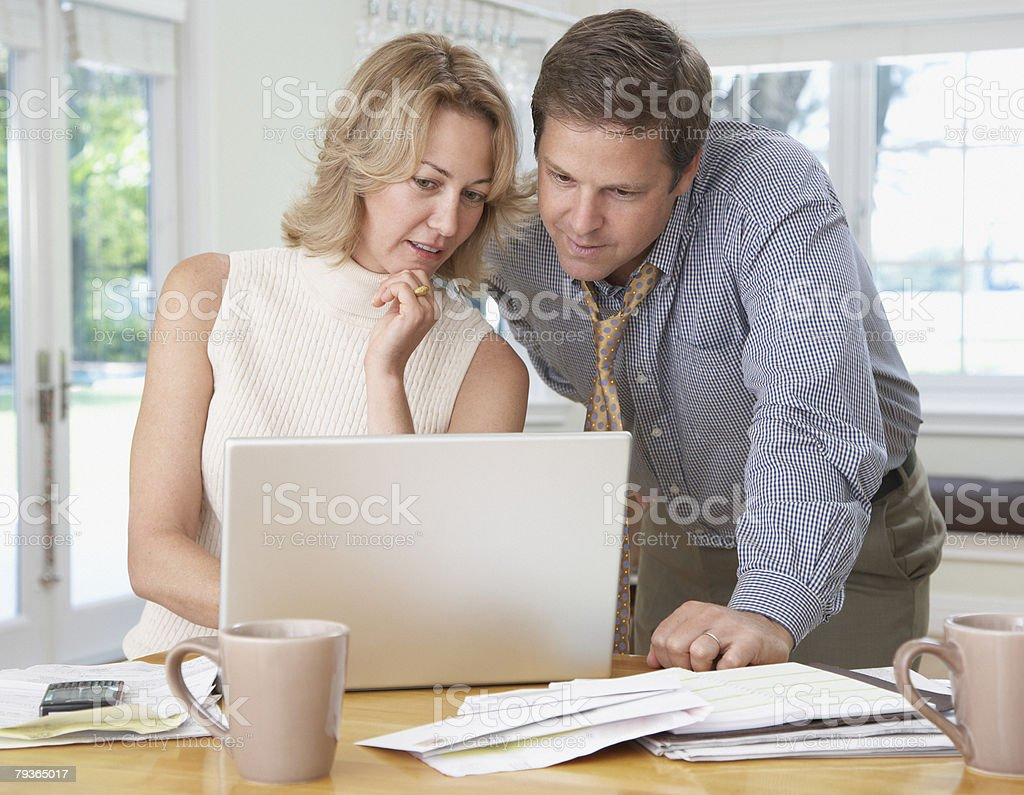 Couple in kitchen with laptop and paperwork royalty-free stock photo