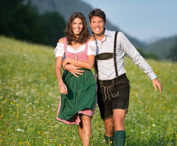 paar in lederhose und dirndl einen spaziergang durch die meadows (xxxl) - bayerische tracht stock-fotos und bilder