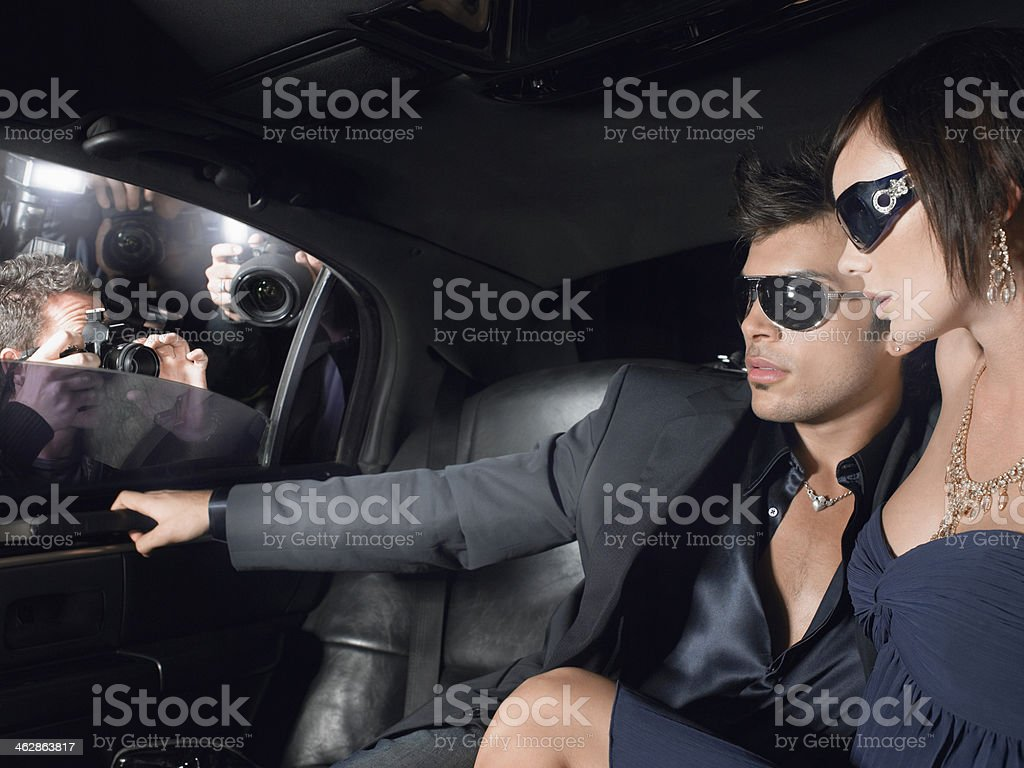 Couple In Limousine With Paparazzi By Window stock photo