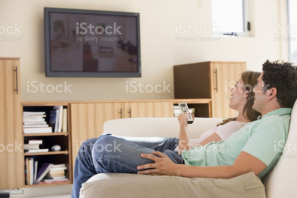 Couple in living room watching television stock photo