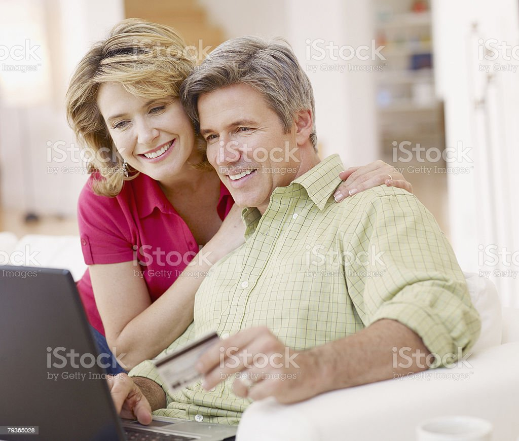 Couple in living room with laptop and credit card stock photo