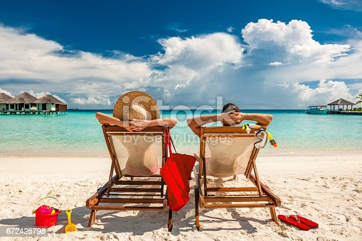 istock Couple in loungers on beach at Maldives 672425798
