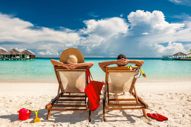 couple in loungers on beach at maldives - idyllisch stockfoto's en -beelden