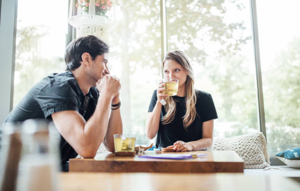 Couple in love at cafe Young couple in love at cafe looking at each other and smiling. Woman drinking green tea and looking at her boyfriend. greentea stock pictures, royalty-free photos & images