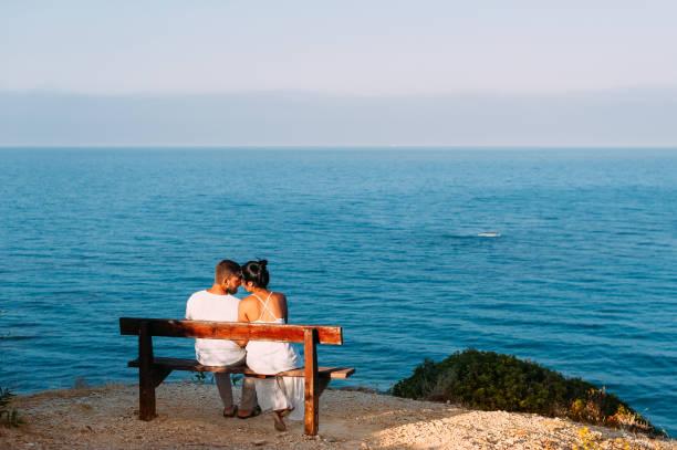 liebespaar bei sonnenuntergang. mann und frau in der dämmerung. paar auf einer bank am meer sitzen. paar küssen am meer. hochzeitsreise. sonnenuntergang am meer. sonnenaufgang am meer. hochzeit reise. sonnenaufgang am ufer - hochzeitsreise zypern stock-fotos und bilder