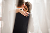 couple in love - brilliant bride brunette and handsome groom - gently embracing on a white background