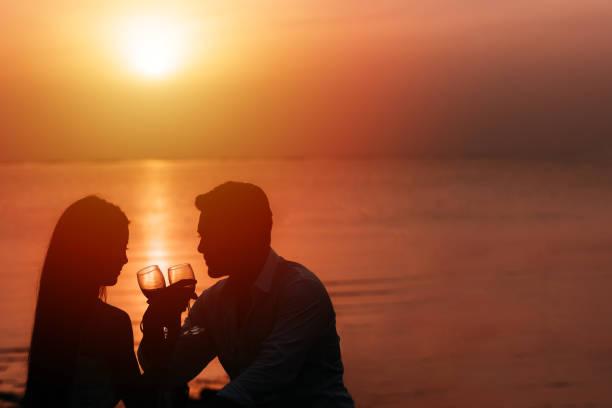 verliebte paar feierte ihren geburtstag am strand - romantisches picknick stock-fotos und bilder