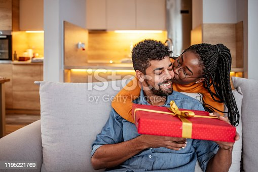 Romantic Couple Exchanging Christmas Gifts At Home. Husband And Wife Affectionately Exchanging Christmas Gifts
