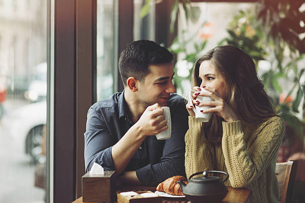 couple in love drinking coffee in coffee shop - couple lap stock photos and pictures