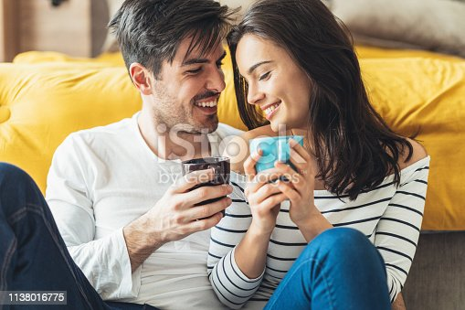 Happy young couple drinking coffee at home spending time together
