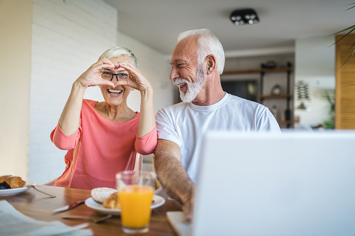 Cute and lovely senior adult couple, spending their time together in love and tranquility, enjoying a morning breakfast.