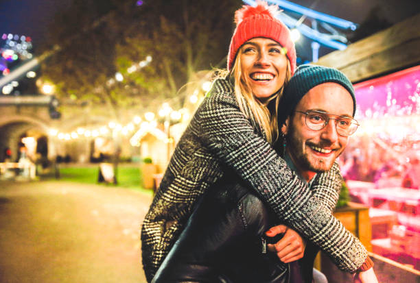 Couple in love enjoying time at the market - Young happy hipster lovers spending evening on dancing and drinking - Happy young hipster couple taking selfie - Focus on mans glasses - Warm red filter stock photo