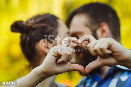 950598260 istock photo Couple in love gesturing heart with fingers. Portrait of brunette and her handsome bearded boyfriend in park 975622944