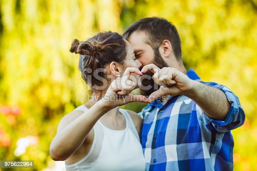950598260 istock photo Couple in love gesturing heart with fingers. Portrait of brunette and her handsome bearded boyfriend in park 975622964