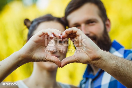 950598260 istock photo Couple in love gesturing heart with fingers. Portrait of brunette and her handsome bearded boyfriend in park 975623000
