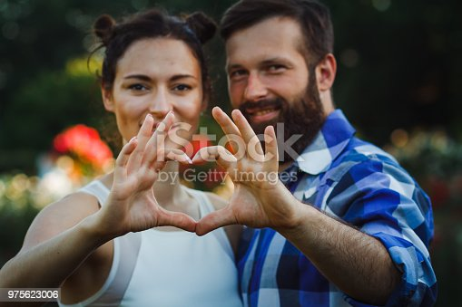 950598260 istock photo Couple in love gesturing heart with fingers. Portrait of brunette and her handsome bearded boyfriend in park 975623006