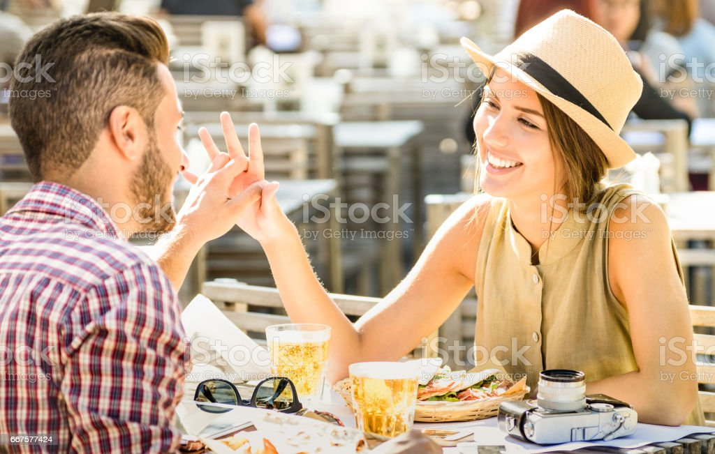 Couple in love having fun at beer bar on travel excursion - Young happy tourists enjoying happy moment at street food restaurant - Relationship concept with focus on girl face on warm bright filter stock photo