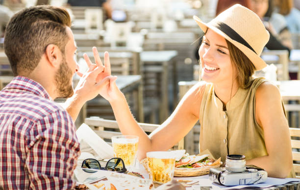 couple in love having fun at beer bar on travel excursion - young happy tourists enjoying happy moment at street food restaurant - relationship concept with focus on girl face on warm bright filter - love at first sight stock photos and pictures