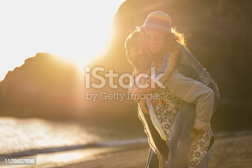istock Couple in love having romantic tender moments at sunset on the beach - Young lovers having tender moments in summer vacation - Love concept - Soft focus on them - Matte filter with soft golden light 1129607696