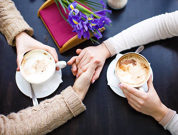 couple in love holding hands in a cafe stock photo