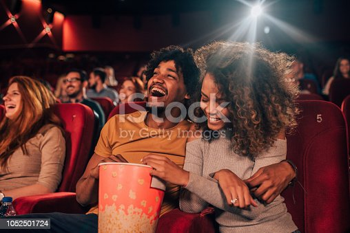 Joyful young people hugging and eating popcorn art the cinema