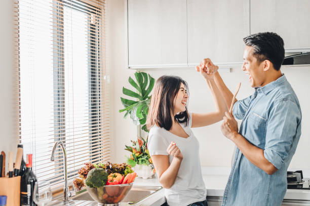 couple in love is dancing and smiling while cooking together in kitchen stock photo