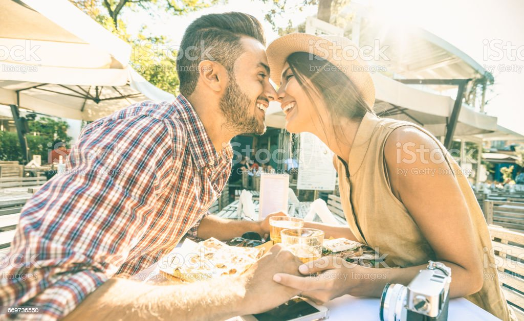 Couple in love kissing at bar eating local delicacie on travel excursion - Young happy tourists enjoying moment at street food restaurant - Relationship concept with lovers at first date - Warm filter stock photo