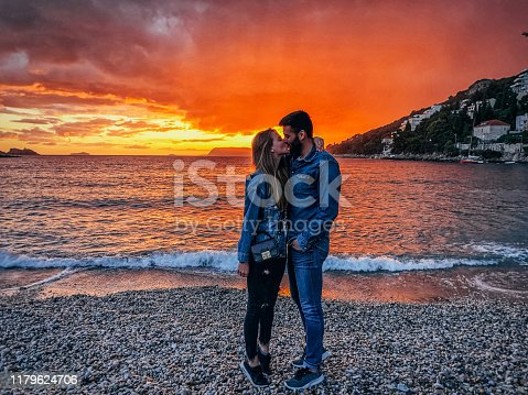 One cute couple in love kissing by the sea, enjoying in sunset.
