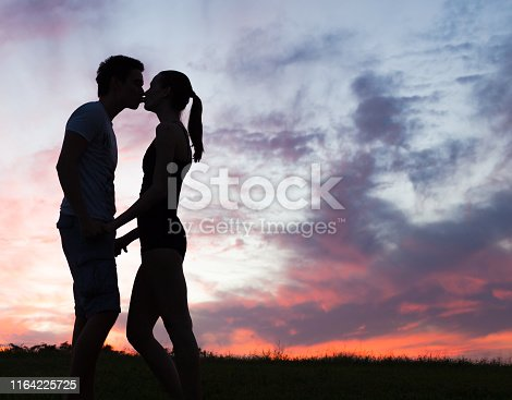 Silhouette of young couple in love kissing.