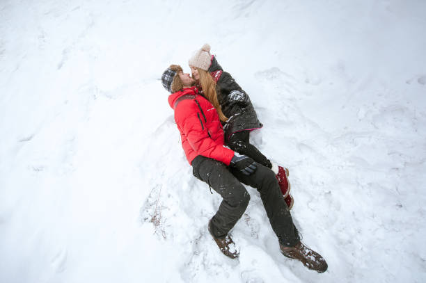 Couple in love lying in the snow stock photo