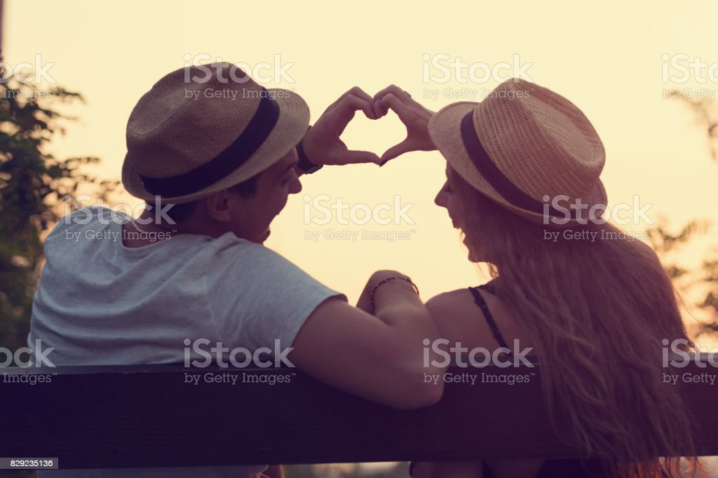 Couple in love making heart shape outdoors. stock photo