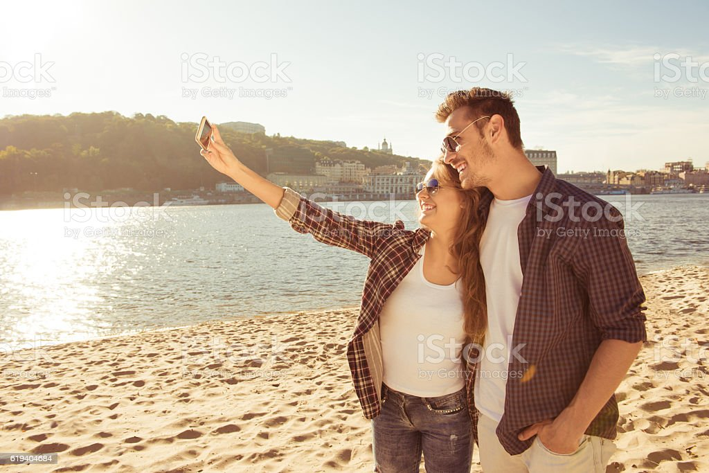 Couple in love making selfie photo at the seaside