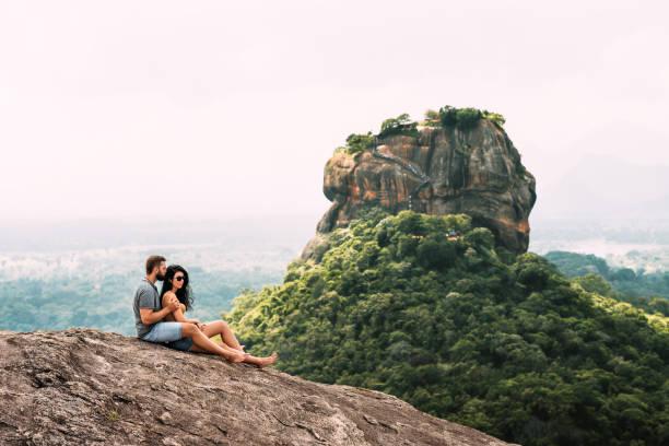 ein liebespaar auf einem felsen bewundert die schöne aussicht. jungen und mädchen auf dem felsen. ein paar in liebe reist. paar in sri lanka. flitterwochen in asien. mann und frau in sigiriya. paar in den bergen - hochzeitsreise ohne mann stock-fotos und bilder