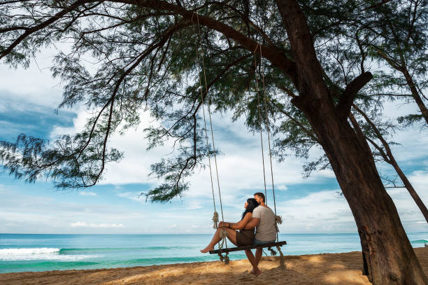 Couple in love on a swing by the sea Guy and girl on a swing by the sea romance stock pictures, royalty-free photos & images