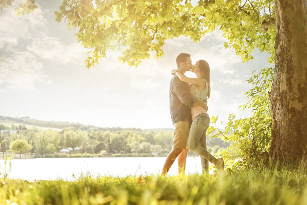 Couple in love on the lake, beneath the trees, kissing stock photo