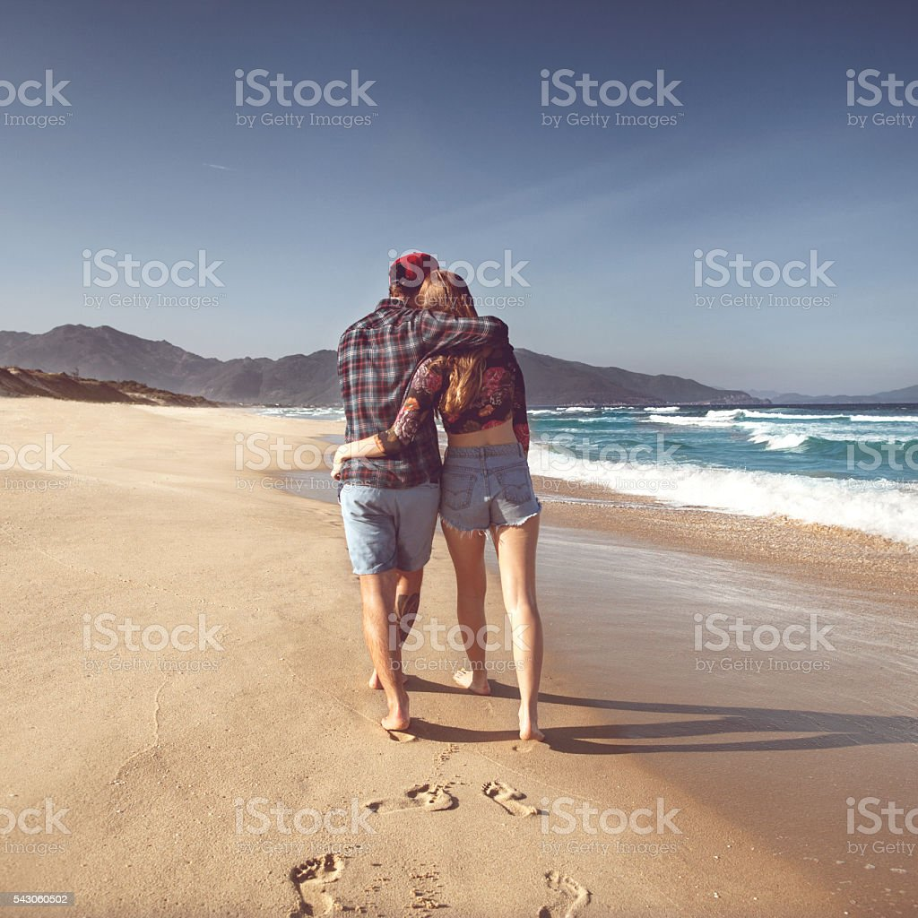 couple in love on the sea playing happily at sunset stock photo
