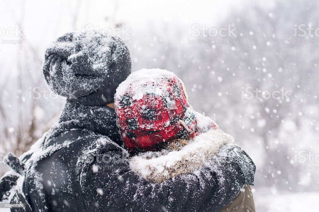 Couple in love outdoors hugging on a winter day stock photo