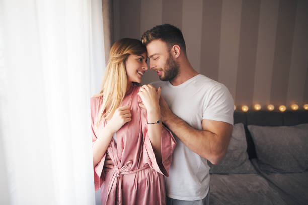 Couple in love Romantic young couple are standing by the window and cuddling real couples making love stock pictures, royalty-free photos & images