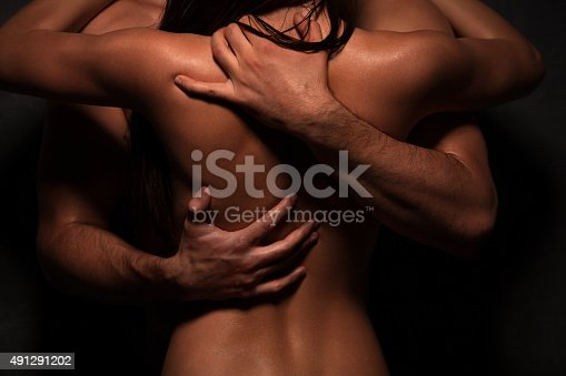 Beautyful sensual couple in love standing semi nude embracing and kissing each other. Man hugging her passionately over her back
