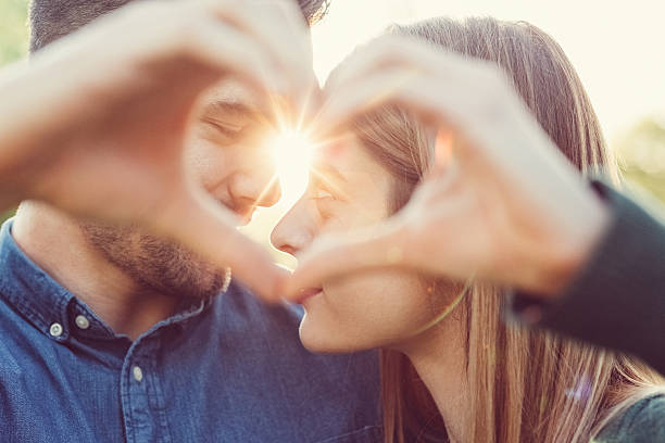 Couple in love Young people showing a heart-shaped symbol with hands love at first sight stock pictures, royalty-free photos & images