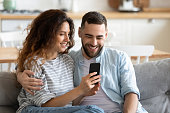 istock Couple in love resting on couch having fun using smartphone 1198401594