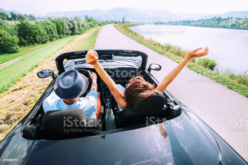 愛のカップルはカブリオレの車に乗る ストックフォト